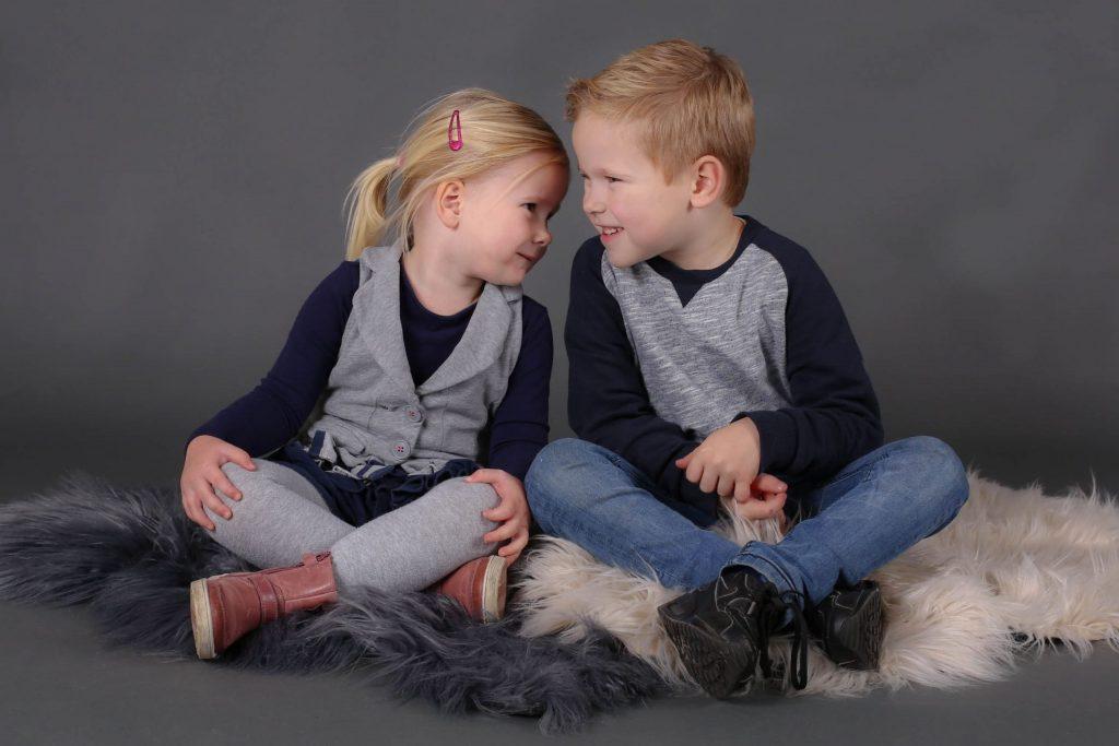 broer en zus poserend op kleed voor familiefotografie