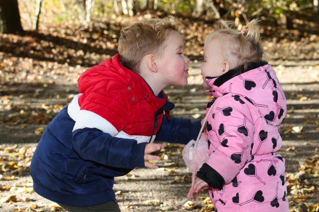 broer en zus geven elkaar kus voor familieshoot