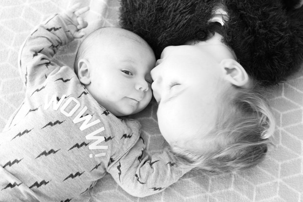 broer met babybroertje liggend op bed voor newborn fotografie