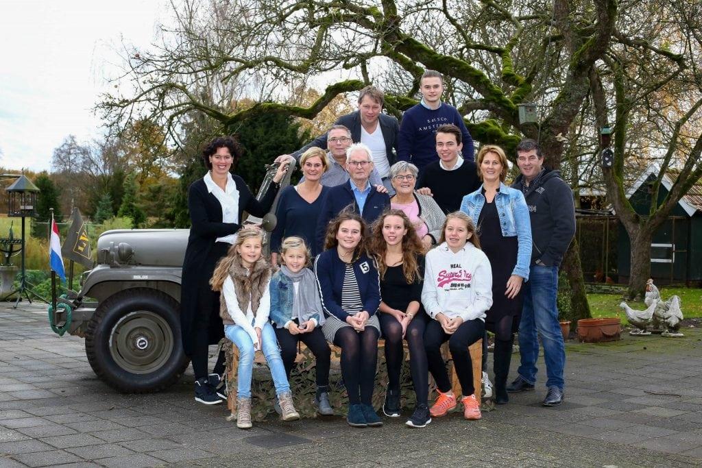 familie poserend tegen oldtimer voor familieshoot