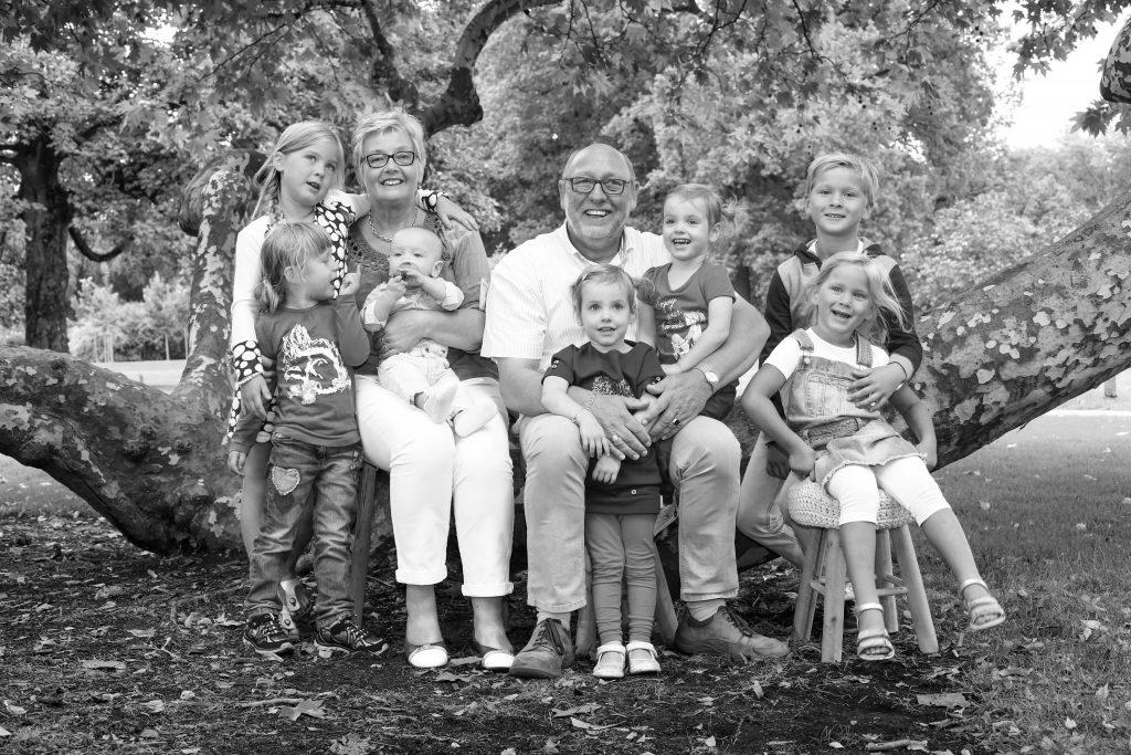 familie poserend bij grote boom voor familieshoot