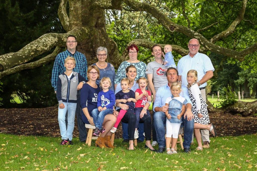 familie poserend bij grote boom voor aanbod familieshoot